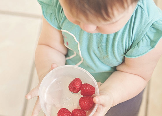 Kind mit einer Schüssel Erdebeeren